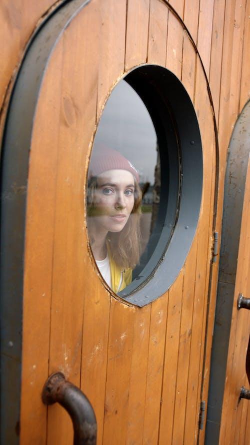 Frau, Die Durch Ein Bullauge Fenster Schaut