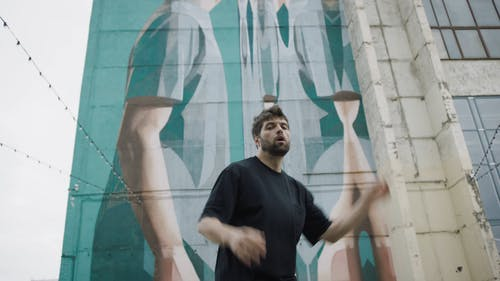 Man Dancing In Front Of A Building With Mural