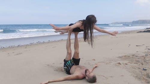 A Man And A Woman Doing A Balancing Act