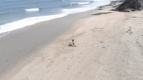 Aerial View Of Two People Doing Balancing On The Beach