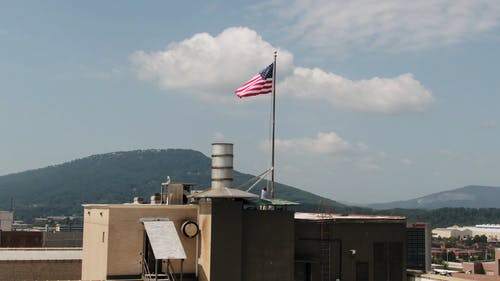 Withdrawing The American Flag From Its Pole On Top Of A Building