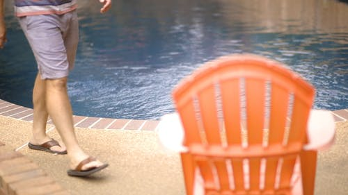 Man Sits On A Chair By The Pool