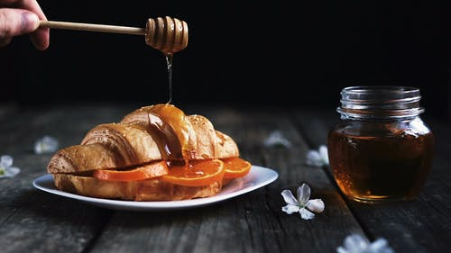 Dripping Honey On A Croissant Bread