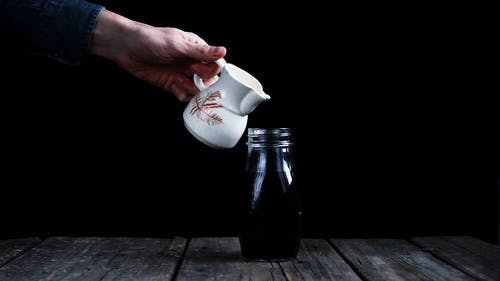 Pouring Milk On A Bottled Black Coffee