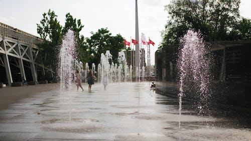 People Having Fun With Water Fountain