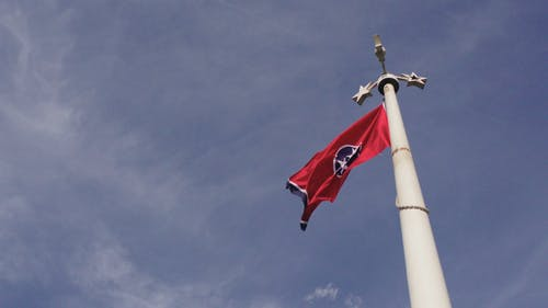 A Flag Sways In The Wind On Its Pole