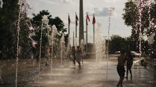 People Getting Wet In A Water Fountain
