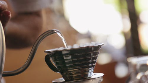 Pouring Hot Water On A Portable Filter Cup Filled With Ground Coffee