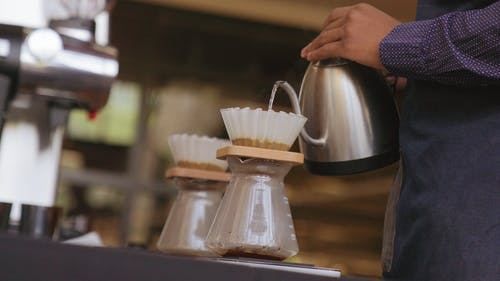 Pouring Hot Water On A Filter Filled With Ground Coffee To Make Brewed Coffee