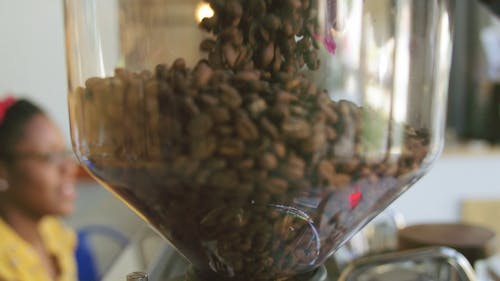 Pouring Coffee Bean To A Glass Container For Grinding