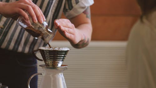 A Man Pouring Ground Coffee On A Tin Cup Filter To Make Hot Brewed Coffee