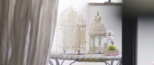 White Candle Lamps With Intricate Design On A Table