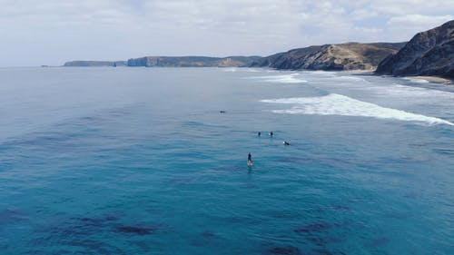 Aerial Footage Of Surfer Paddling Across The Sea With Scenic View Of The Mountains
