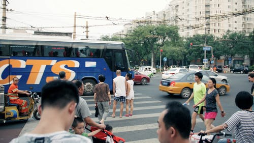 People Waiting To Cross A Street On The Pedestrian Lane