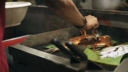 Grilling A Fish Over A Banana Leaves