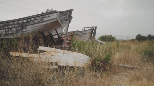 An Abandoned Boat In A Grassfield