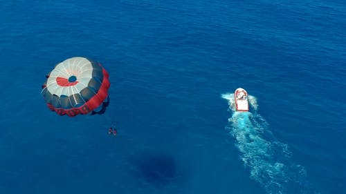 A Couple Paragliding Over The Blue Water  Of The Sea