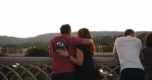 A Couple Show Their  Love By Kissing On A View Deck