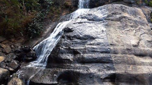 Uma Queda D'água Em Cascata Por Uma Grande Formação Rochosa