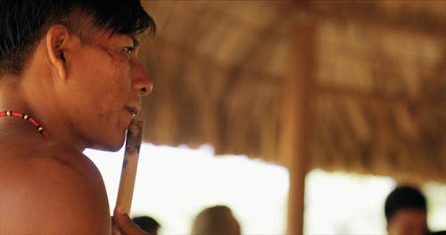 A Tribe Man Playing A Musical Instrument