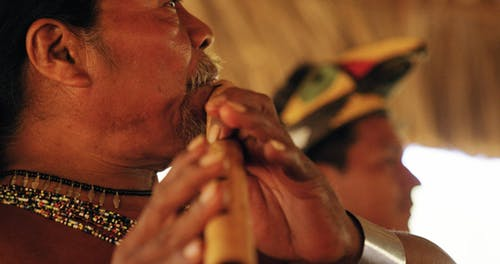 Slow Motion Footage Of A Elderly Man Playing A Traditional Wooden Wind Musical Instrument
