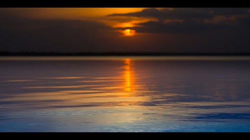 Low Angle Footage Of The Glassy Surface Of The Sea Reflecting The Sunlight  Across The horizon At Dusk