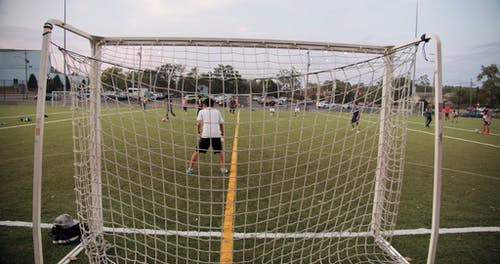 A Goalie Guarding The Net In A Game Of Football