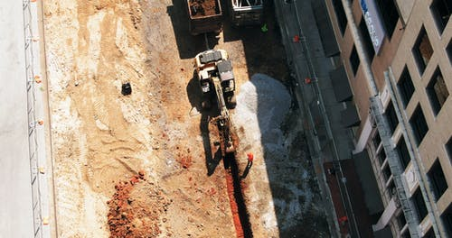 Aerial Footage Of A Backhoe At Work On A Construction Site