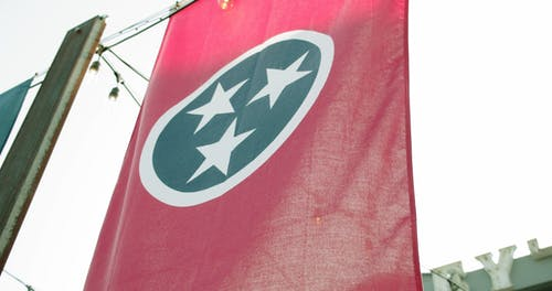 The Flag Of Tennessee Hanging Vertiacally From A Suspended Line