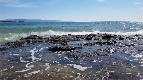 Волны разбиваются о скалистый берег