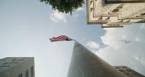 The American Flag Raised High In A Flag Pole