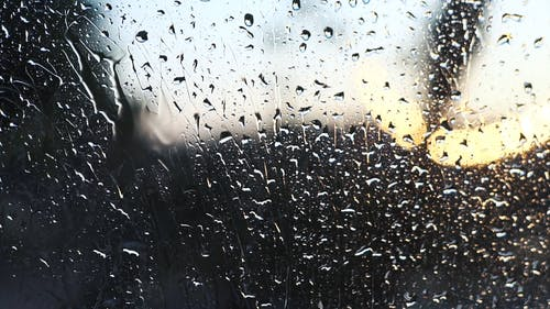 Close-up Of Raindrops Dripping Down A Glass Window On A Rainy Day