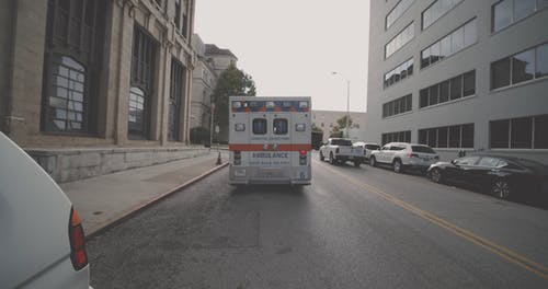 An Ambulance Parked On A Street With Emergency Flashers On