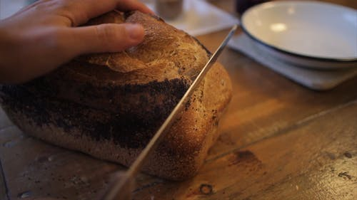 Slicing A Loaf Of Bread Using A Bread Knife