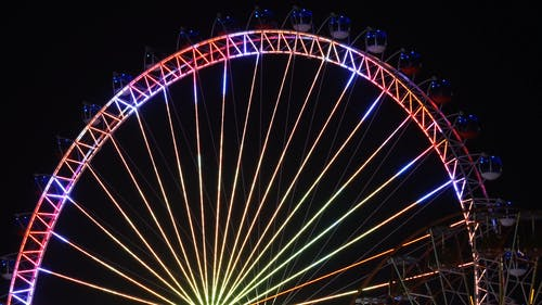 An Observation Wheel With Illuminated Dancing Lights At Night