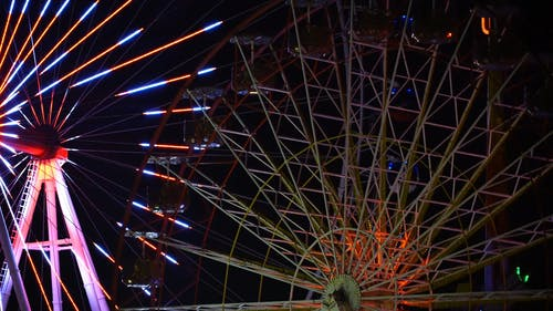 Moving Ferris Wheel Surrounded with Dancing Neon Lights