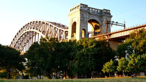 People Enjoying The Park Under The Hell Gate Bridge in New York