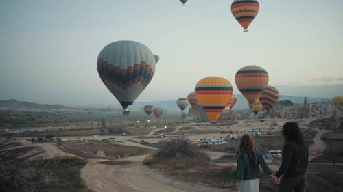 Slow Motion Footage Of A Couple Walking Hand In Hand Towards The Take-off Site Of Hot Air Balloons