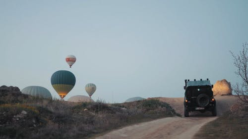 A 4x4 Vehicle Driving On Rugged Dirt Road Towards The Take-off Site Of The Hot Air Balloons