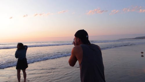 Man Taking A Photo Of A Woman While Taking A Picture Of The Sea With Her Back Turned