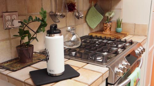 A Vacuum Flask On The Counter Besides The Stove