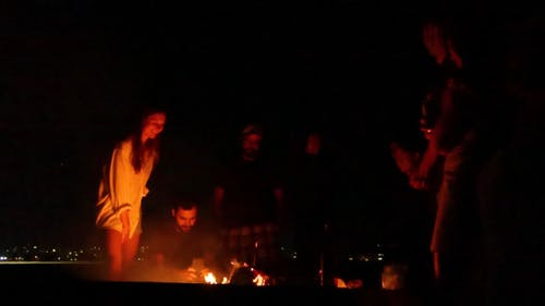 Men And Women Gathers Around a Bonfire At Night