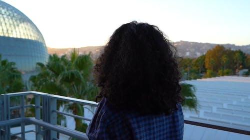 De Achterkant Van Een Persoon Met Krullend Haar En Draagt Een Geruit Shirt