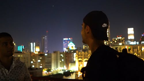 Two Men Talking With Each Other At The View Deck Of A Roof Top