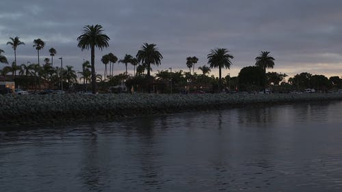 Silent Flow Of A River With People Walking Along The Banks In A Community At Dusk