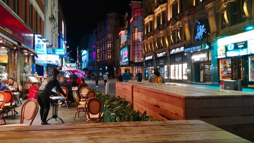A Waitress Gathers The Table And Chairs Of A Restaurant Arranged In The Sidewalk