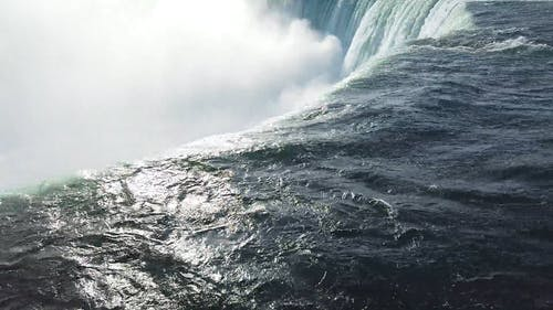 The Downward Force Of The Niagara Falls Produces Mist Of Water