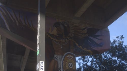 A Mural Painted On The Wall Of The Support Beam Under A Bridge
