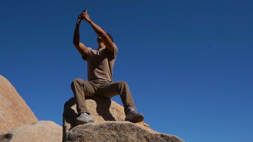 A Man Taking Selfie On Seated On A Boulder Of Rock