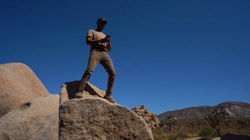 Low Angle Footage Of A Man Standing On A Boulder Taking A Selfie With The Background Of The Desert Landscape
